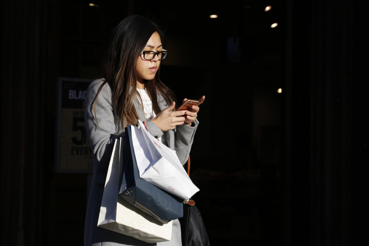 A pedestrian looks at her smartphone as she carries a Uniqlo, operated by Fast Retailing Co., branded shopping bag as she walks on Regent Street, in London, U.K., on Friday, Nov. 25, 2016. Black Friday first became a part of U.K. shopping culture in 2014 when a rush for bargains saw fights break out as crowds gathered outside stores, in 2016 however, only 21 percent of British consumers interviewed by consultant Retail Economics said they plan to shop for Black Friday bargains. Photographer: Luke MacGregor